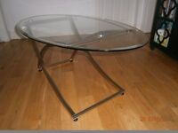 stylish oval glass topped coffee table with stainless steel shaped legs.
