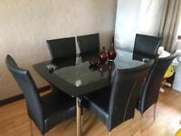Harveys boat glass double teir dining table & 6 black leather chairs.