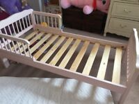 Pink wooden toddler bed with mattress