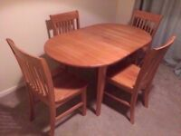 Extendable solid oak dining table set with 4 chairs.