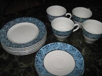 A set of 4 cups, saucers, and plates blue with gold pattern