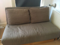 Solid oak linear two seat sofa bed by Futon Company with trifold mattress and two pillows