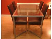 Glass dining table with four brown leather chairs