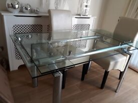 Clear glass and chrome dining table