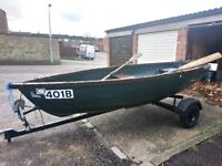open rowboat with outboard and trailer