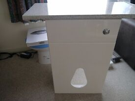 Gloss white wc unit with granite effect worktop.