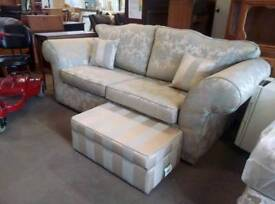 Large patterned fabric two seater sofa with small ottoman