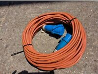 Long orange electric mains hookup cable