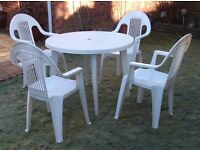 Garden table and four plastic chairs