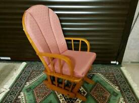 Pink upholstered cushioned nursing / gliding chair