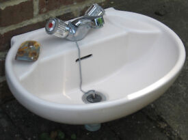 Small pink washbasin with taps and plug
