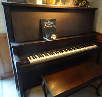 Antique upright piano in working condition, bench included.