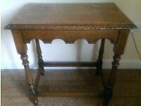 AN ANTIQUE CARVED OAK SIDE TABLE