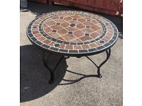 Unused mosaic patio table with fire pit and barbecue options