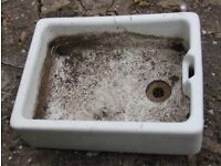 Belfast sink, used as a planter on a patio.