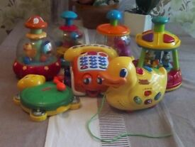 Selection of children's toys including four spinning tops, pull along telephone, duck, drum.