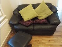 2 seater - black leather sofa in good condition size 150cm (l)x75 (w)and one leather foot stool