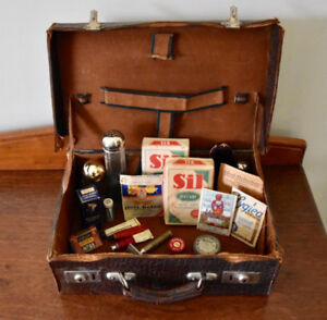 Antique suitcase with quirky array of antique household items