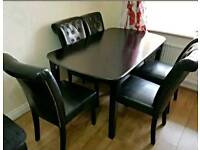 Black wooden extendable dinning table with 6 faux leather chairs