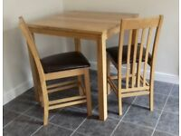 Oak kitchen table and two chairs.