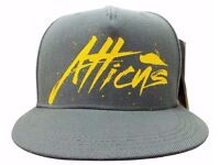 Atticus Snapback Baseball Cap. New & Sealed. Grey with yellow logo.