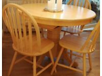 Solid pine extending dining table with 4 chairs .