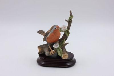 Singvogel Rotkehlchen auf Ast sitzend + Holzsockel