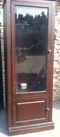 Tall dark stained wood cabinet w lighting and glass shelves
