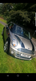 Gold mini Cooper hatchback. Excellent cheap to run and tax car.