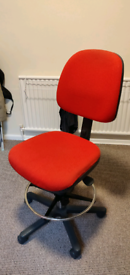 Red office swivel chair with foot stand