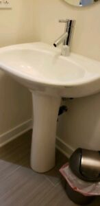 White pedestal sink with Moen faucet and mirror