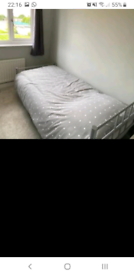 Single metal framed bed with mattress and full bedding set.