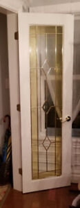 Two white french door with beveled and coloured glass inserts.