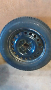 """4 steel rims 5 bolt with 215 / 65r / 17"""" studded winter tires."""