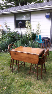 Antique drop leaf table and 4 spindle chairs.