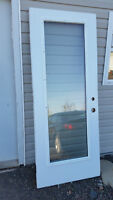 "Used 32x80 exterior door with 20""x66"" clear glass"