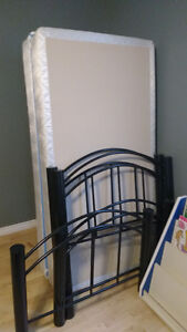 Two black steel bed frames with box springs