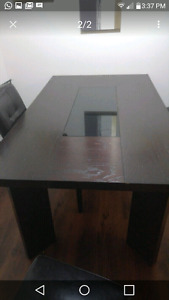 Dark heavy wood dining table with black glass center seats 6