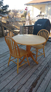 Small wooden drop leaf table and two chairs