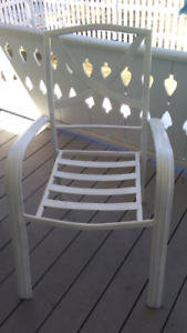 Two white metal patio chairs