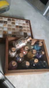 Various tiny gemstones in corked bottles set in wooden box