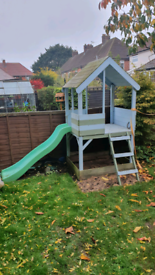 Wooden playhouse with slide and sandbox