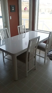 white kitchen or dining table with 4 designer chairs
