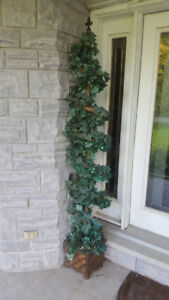 Tall spiral artificial outdoor potted trees to flank front door.