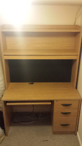 Large wooden desk with cork board, hutch, and a built in light