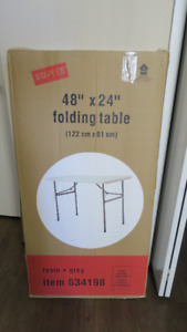 """Staples 48"""" by 24"""" resin folding table."""