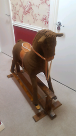 Brown rocking horse with saddle and rein and stirrups