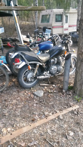 A bunch of old motorcycles, dirtbikes, lawn tractors, rototiller