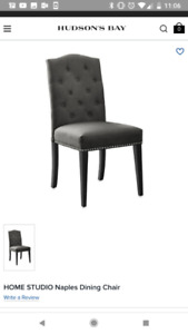 Eight gray tufted dining chairs and long black dining table