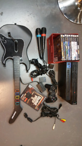 Playstation 2 with guitar hero, singstar mics, and 9 games